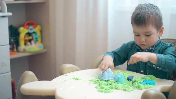 A little boy builds castles and various figures of green kinetic sand
