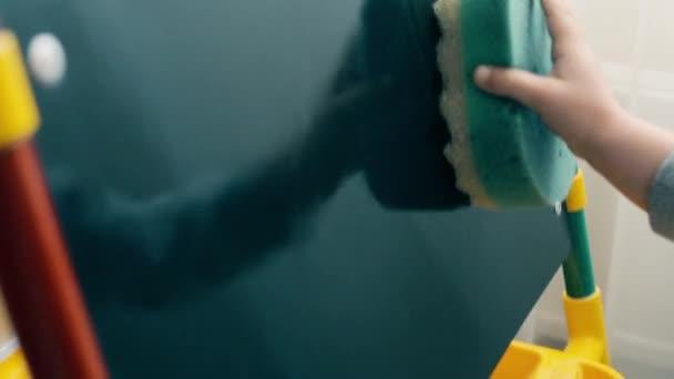 das Kind wischt die Kreide mit einem feuchten Schwamm vom Brett