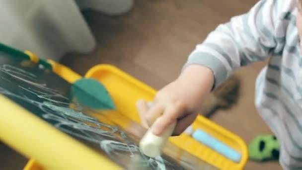 Sladké dítě naučit se kreslit křídou na tabuli