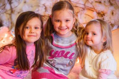 three girls hug and smile in the New Year decorations with artificial snow and small cardboard houses