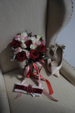 wedding accessories on a beige armchair: a bride's bouquet of red and pink roses, women's shoes, a garter of the bride