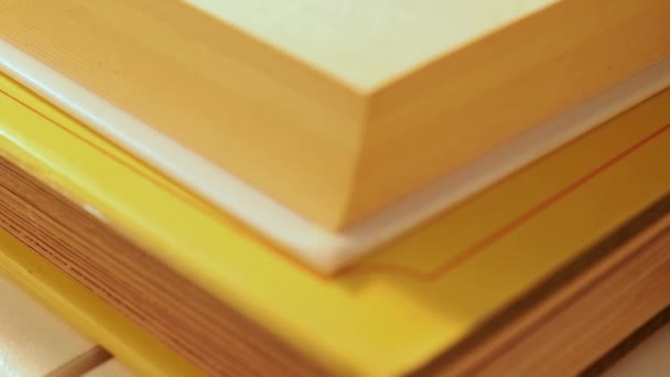 Stack of books ,yellow dried flower of daffodil on top  , beautiful shadows ,pan from below upwards