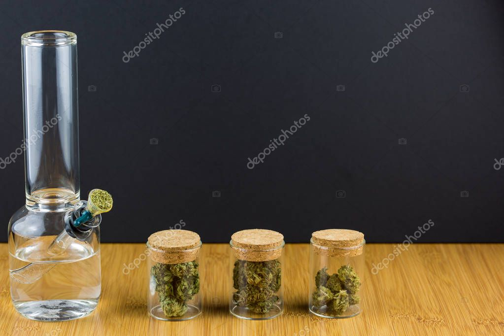 Glass containers filled with medical marijuana in a row with glass bong on wood surface against a black background