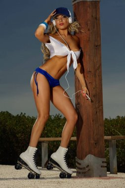 Sexy blonde girl on roller skates listening to music player