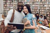Etnikai multikulturális tanulócsoport ül asztal könyvtár, fekete srác, és asial a lány segítségével tabletta