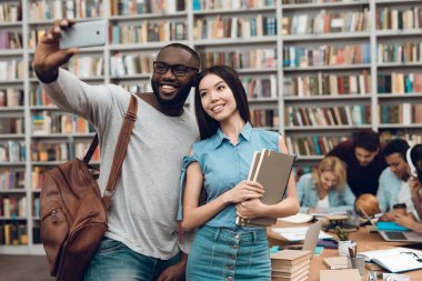 Group of ethnic multicultural students sitting at table in library, black guy and asian girl taking selfie on smartphone