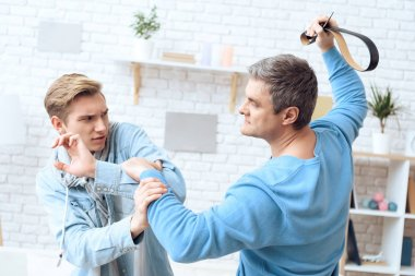 Father hitting with belt son while teenager trying protect oneself