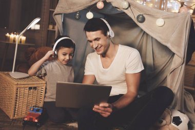 Father and son listening music on laptop at home