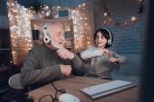 Großvater und Enkel hören zu Hause Musik über Kopfhörer