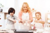 Fotografie Young grandmother with grandchildren preparing cookies at kitchen
