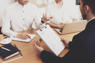 HR director woman in blouse and skirt discussing resume with men at job interview