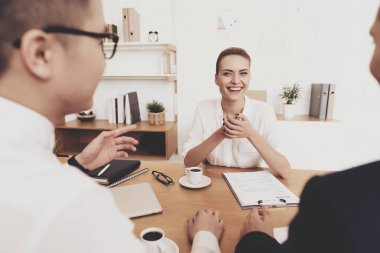 HR director woman in blouse and skirt sitting with workers and asking questions at job interview