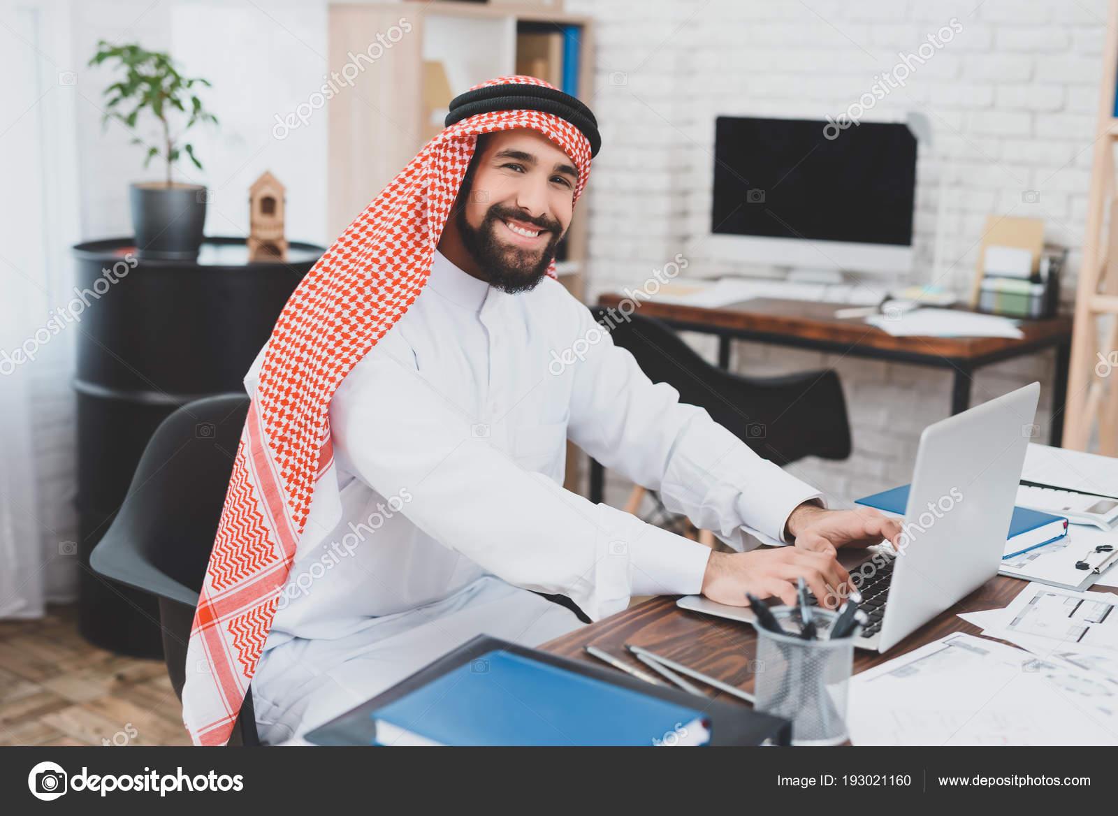 Homme arabe satisfait keffiyeh dactylographie sur ordinateur