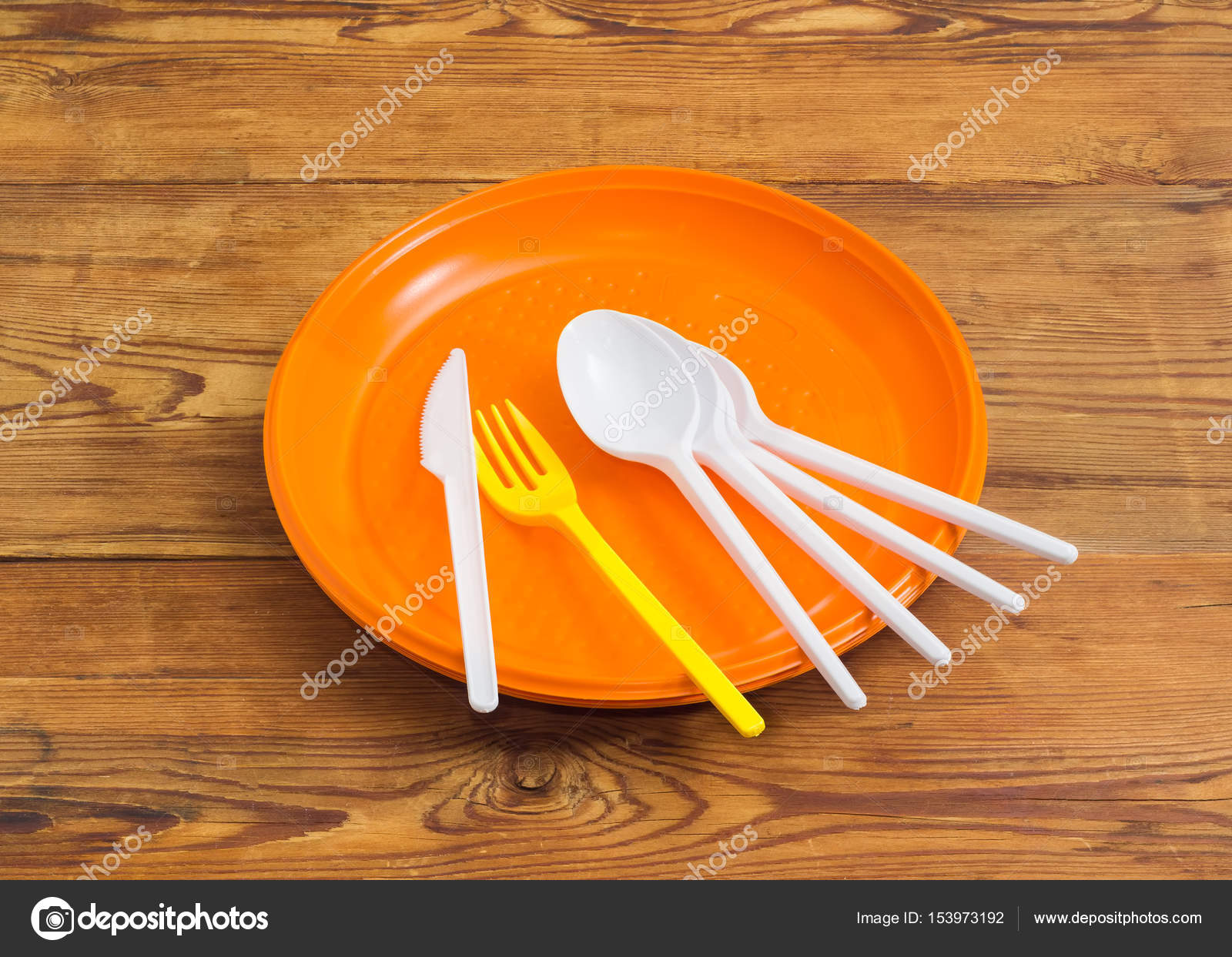 Several disposable plastic white spoons knife yellow fork on the pile of the orange plastic disposable plates on a surface of the old wooden planks ... & Disposable plastic plates spoons fork and knife on wooden surface ...