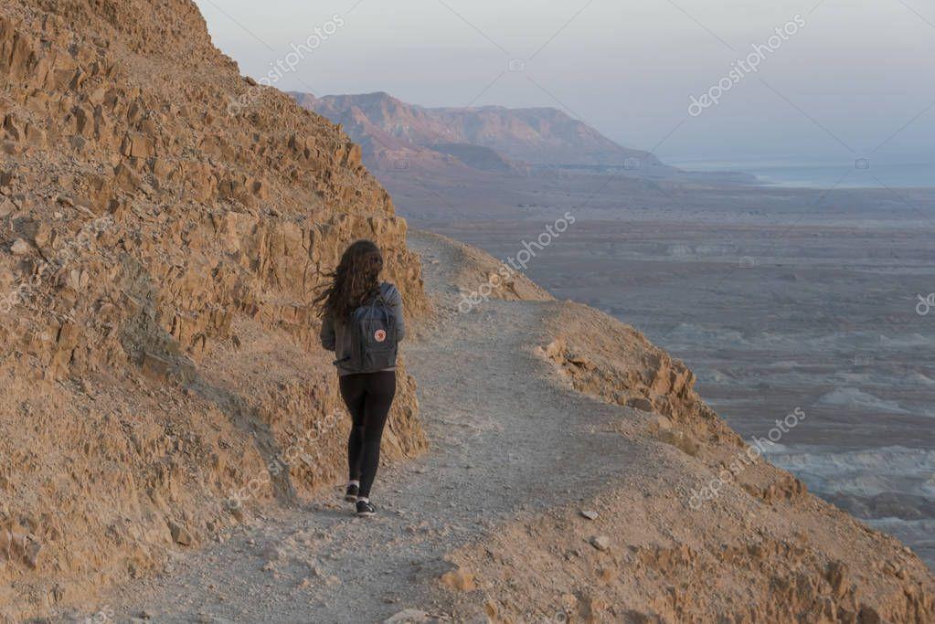 Rear view of teenage girl walking at abandoned fort, Masada, Judean Desert, Dead Sea Region, Israel
