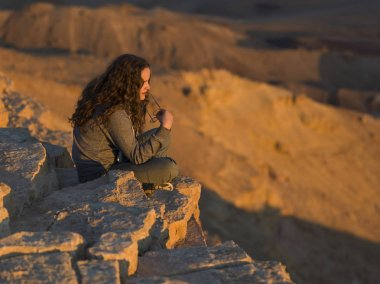 View of teenage girl sitting on rock in desert, Makhtesh Ramon, Negev Desert, Israel