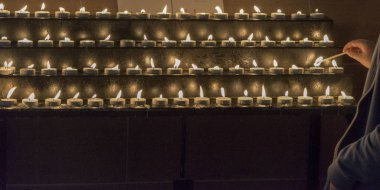 Person lighting  church votive candles at St Giles Cathedral, Edinburgh, Scotland
