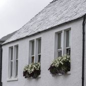 Low angle view of a house with flower boxes, Portree, Isle of Skye, Scottish Highlands, Scotland