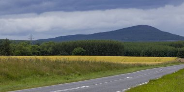 Empty road passing through rural landscape against cloudy sky, Scotland