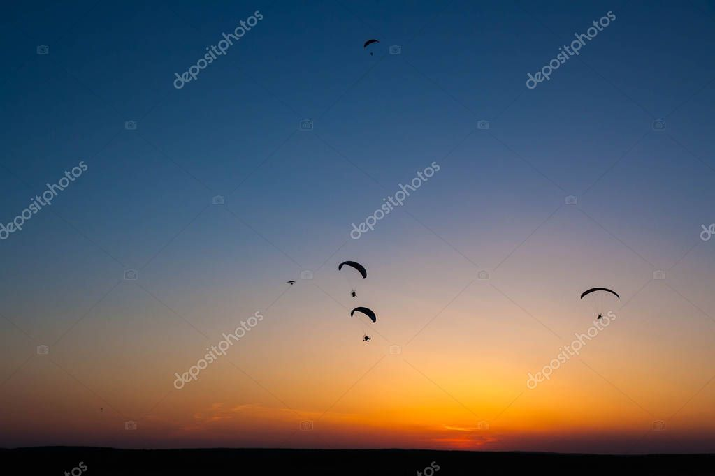 The dark silhouettes of paramotors for powered paragliding flies in the sky against the background of a bright red sunset