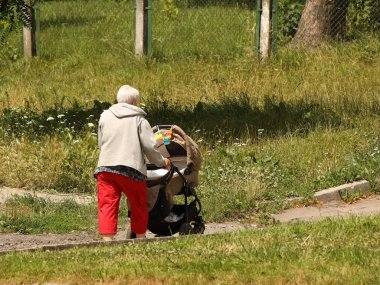 An elderly woman walks with a pram among the summer greenery. A governess is nursing a child on the street. Raising children zorovym and seasoned. Baby sleep in the fresh air. Socialization of older