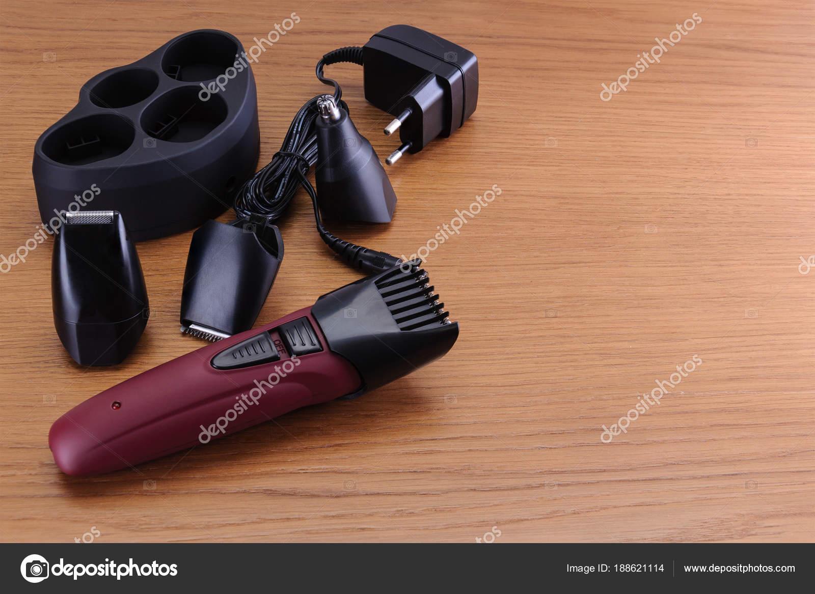 Ηλεκτρικά εργαλεία χειρός κουρευτική μηχανή με βάση και αξεσουάρ για τα  μαλλιά κομμωτήριο ή κουρείο κατάστημα στο ξύλο παρασκήνιο με αντίγραφο  χώρου ... a91a9d5f7c6