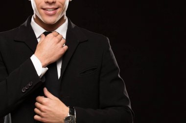 Cropped shot of a handsome man wearing elegant black suit smiling adjusting his tie on black background copyspace positivity confidence businesspeople success preparing preparation wellbeing