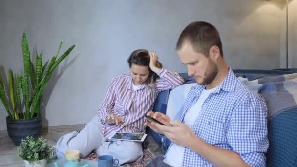 Young couple with her smartphone in their new home. Happy couple with working with smartphone and documents sitting on floor at new