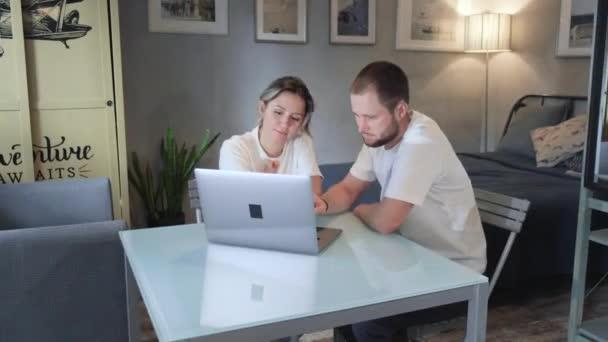 Porträt eines jungen Paares, das zu Hause vor einem Notizbuch sitzt. Schöner brünette mann und süß blond frau working at.