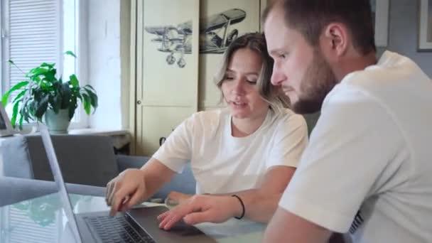Bleiben Sie zu Hause. Schönes Paar zu Hause. Mann arbeitet zu Hause, er ist während der Quarantäne freiberuflich, er benutzt Laptop.