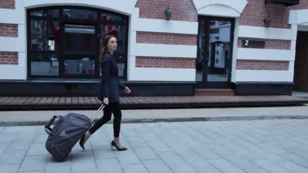 Back view of tourist woman in black. View of female legs walking with a suitcase in the street.