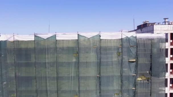 Letecký pohled na dům ve výstavbě. Nedokončená cihlová budova s rámem pro střechu.