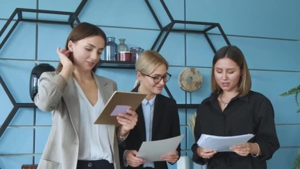 Three colleagues communicate and make a presentation. Three beautiful business women are standing in office and discussing project, idea, plan