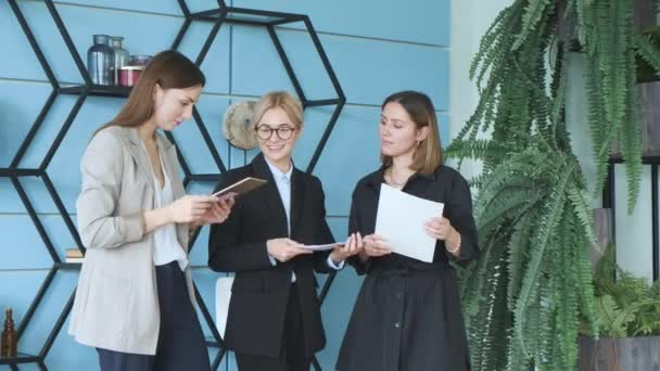 Three beautiful young girls in business suits. Business style. Girl, casual. Female business people finding document and discussing plan on paper. Three young girls coworkers in conference room talking on project.