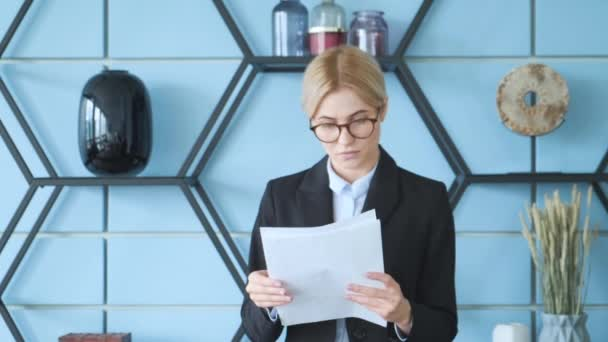 A young business girl stands in the office and looks at documents for a new project