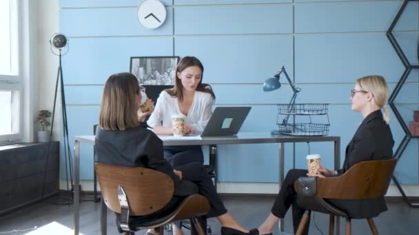 Three business girls are sitting on chairs at a table drinking coffee and discussing new projects. Three colleagues communicate and make a presentation.