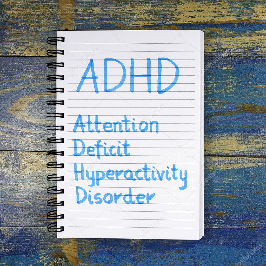 ADHD- Attention Deficit Hyperactivity Disorder written in noteboook on wooden background