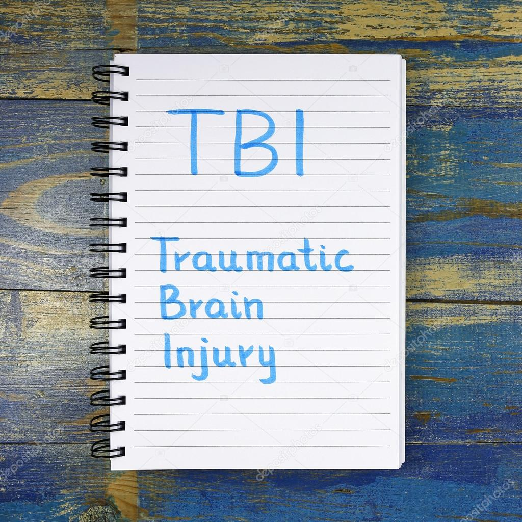 TBI- Traumatic Brain Injury acronym written in notebook on wooden background