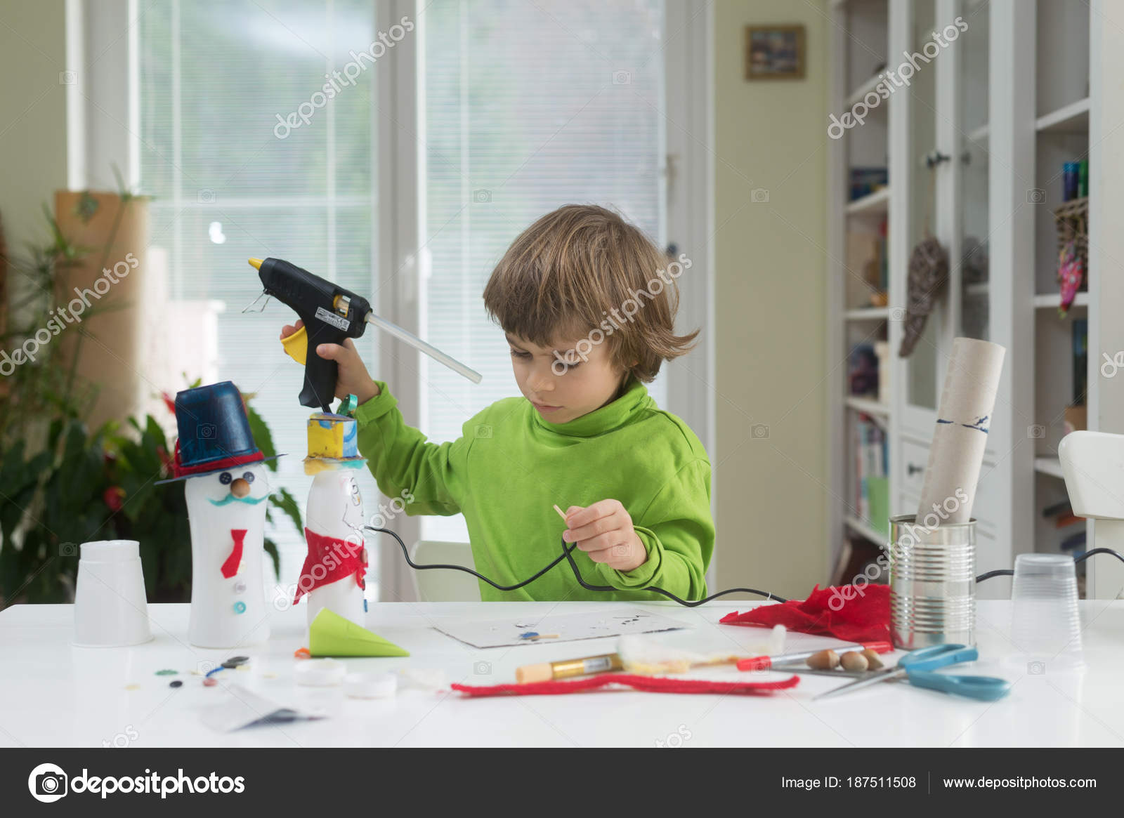 Little boy being creative making homemade yourself toys out yogurt little boy being creative making homemade do it yourself toys out of yogurt bottle and paper using hot melt glue gun supporting creativity learning by solutioingenieria Images