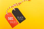Internetes vásárlás, Promóció Fekete péntek szöveg fekete címkére és 50% eladó szöveg piros címkére sárga háttérrel