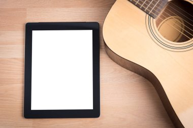 Acoustic guitar with digital tablet on the wooden table