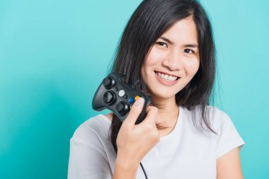 Portrait Asian beautiful happy young woman wear t-shirt gamer with a joystick or gamepad in hands, on blue background