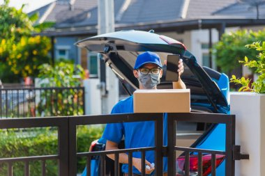 Asian delivery man courier Place deliveries boxes at home and showing mobile phone blank screen for customer sign he protective face mask service under curfew quarantine pandemic coronavirus COVID-19