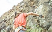 Photo Man giving security to woman who is climbing up on mountain cliff - Climber in action on the rock near the peak - concept of extreme lifestyle, adrenaline and sport
