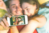 Fotografie Young couple of lovers taking lying on grass taking a selfie with mobile phone - Happy teenagers in love making a self portrait using smartphone camera - Warm vintage filter -