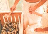Mladý pár, drželi se za ruce s relaxovat v sauně v spa resort hotel - muž vylévající vodu se lžící na horké kameny - pojem relax a péče o tělo - zaměření na mužské ruky