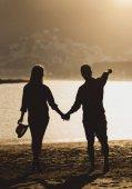 Fotografie Zadní pohled na krásný mladý pár teenagerů drží ruce stojící na pláži při západu slunce - Silhoutte dvou milenců s romantickým posezením na pláži - láska a dovolené koncept