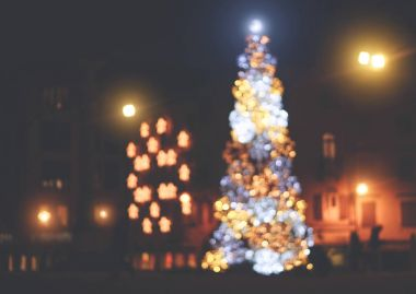 Blurred christmas tree with colorful bright lights in the city at night - Defocused image - Concept of holiday, christmas decoration