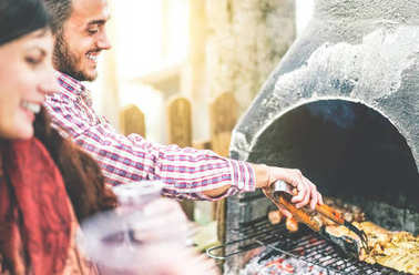 Happy young friends making a barbecue party grilling meat in the backyard - Handsome man cooking grilled beef for his friends - Concept of people, food, lifestyle and friendship - Focus on male hand