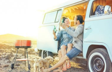 Travel couple having fun drinking beers sitting on their vintage camper mini van - Happy people with their pet enjoying barbecue at sunset during a roadtrip - Concept of vacation lifestyle and love